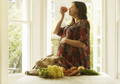 Pregnant woman smelling orange with her eyes closed