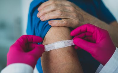 Older woman receives a vaccine and doctor is placing bandaid on her arm.