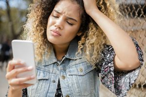 A woman with furrowed brows holds her head and looks at her phone