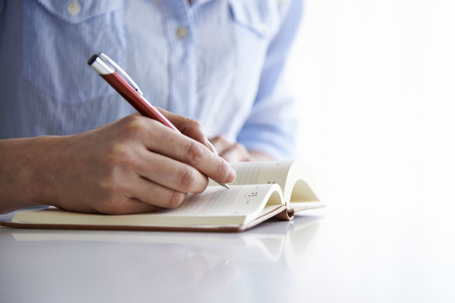 Close up of hands writing in a journal