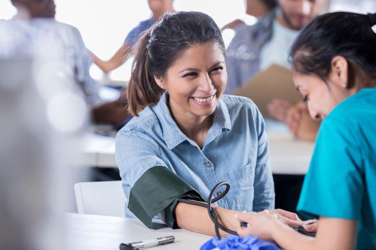 a nurse checks patient's blood pressure