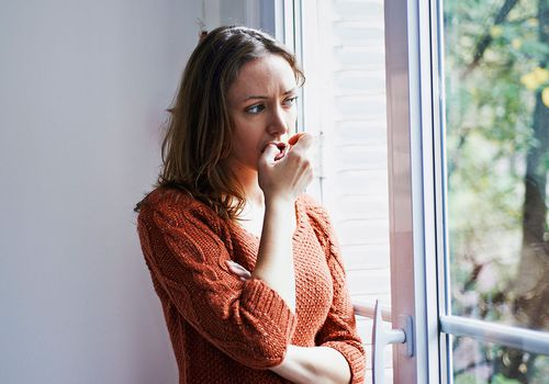 Worried woman looking out a window