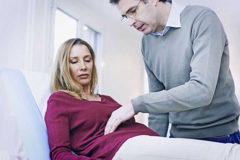 doctor examining female patient's abdomen