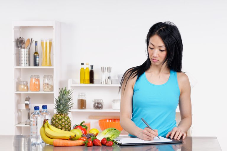 asian woman looking at fruit and vegetables and writing