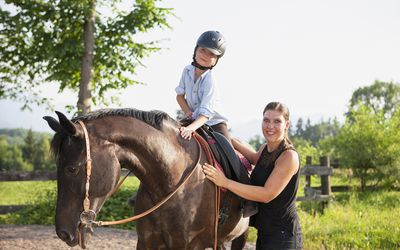 Child on horse with therapist