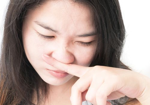 Close-Up Of Woman Rubbing Nose Against White Background