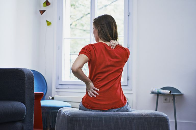 A woman sitting down with severe back pain