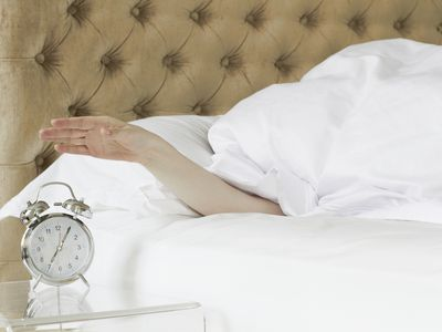 Person in bed reaching for an alarm clock
