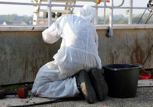 man in protective gear to prevent pneumoconiosis working with asbestos