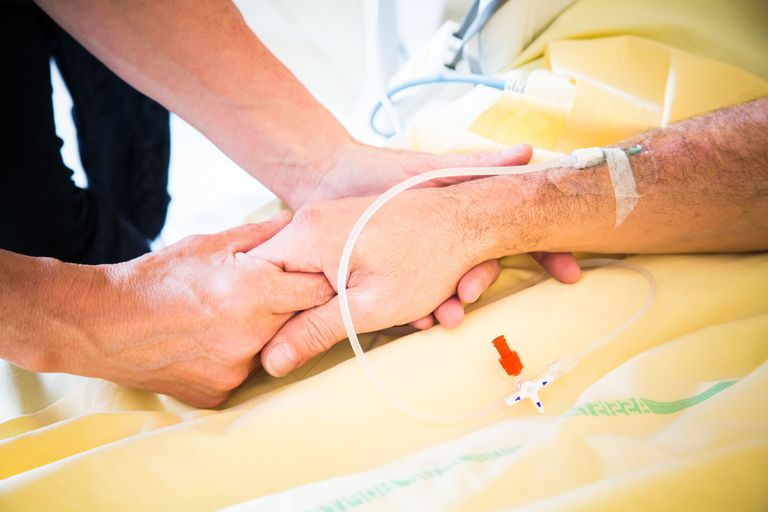 Person holding another person's hand (with an IV) in the hospital