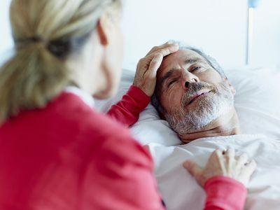 Woman caressing ill man in hospital ward Rear view of woman caressing ill man in hospital ward