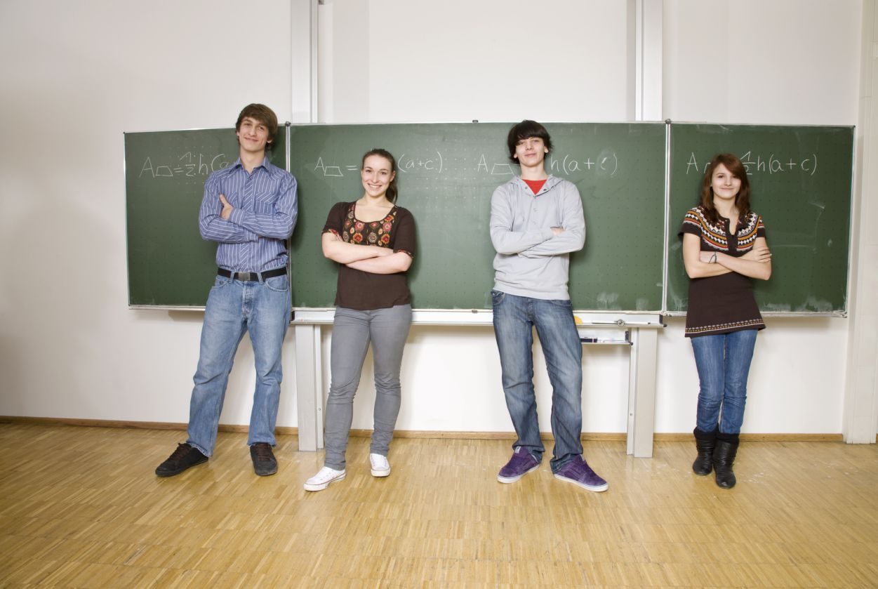 Fours teenagers standing with arms crossed at the front of a classroom