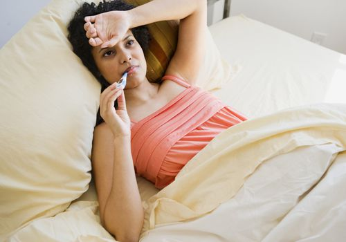 Woman laying in bed sick