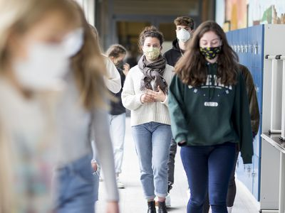 Teenagers walking down a high school corridor wearing face masks