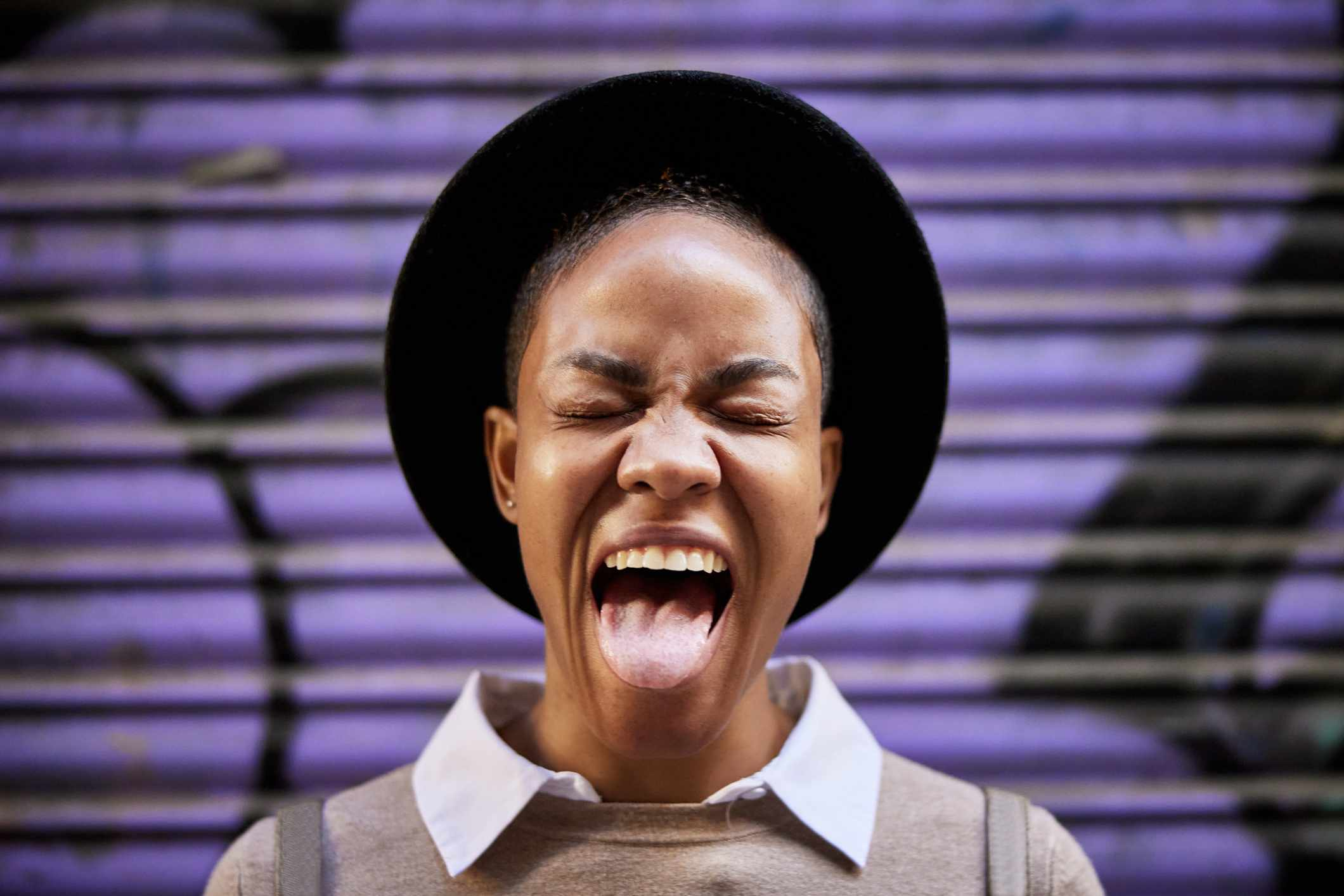 Woman grimacing and sticking out tongue