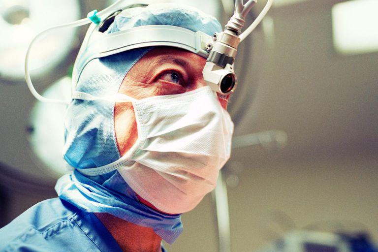 Brain surgeon wearing medical head light helmet, close-up