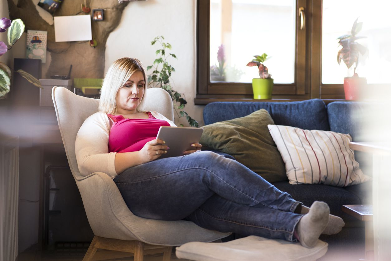 Woman reclined in a chair reading a tablet