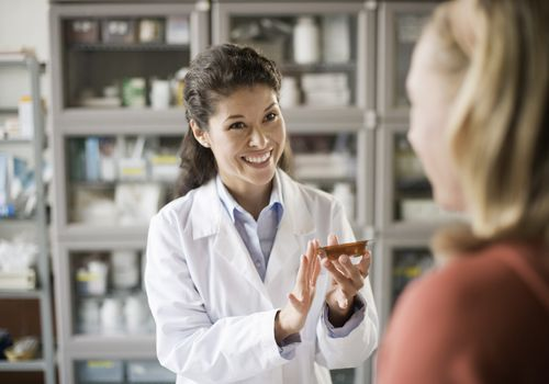 A pharmacist explaining a drug to a customer