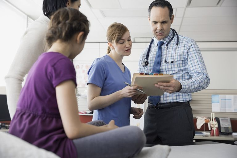 Pediatrician and nurse reviewing medical record in office