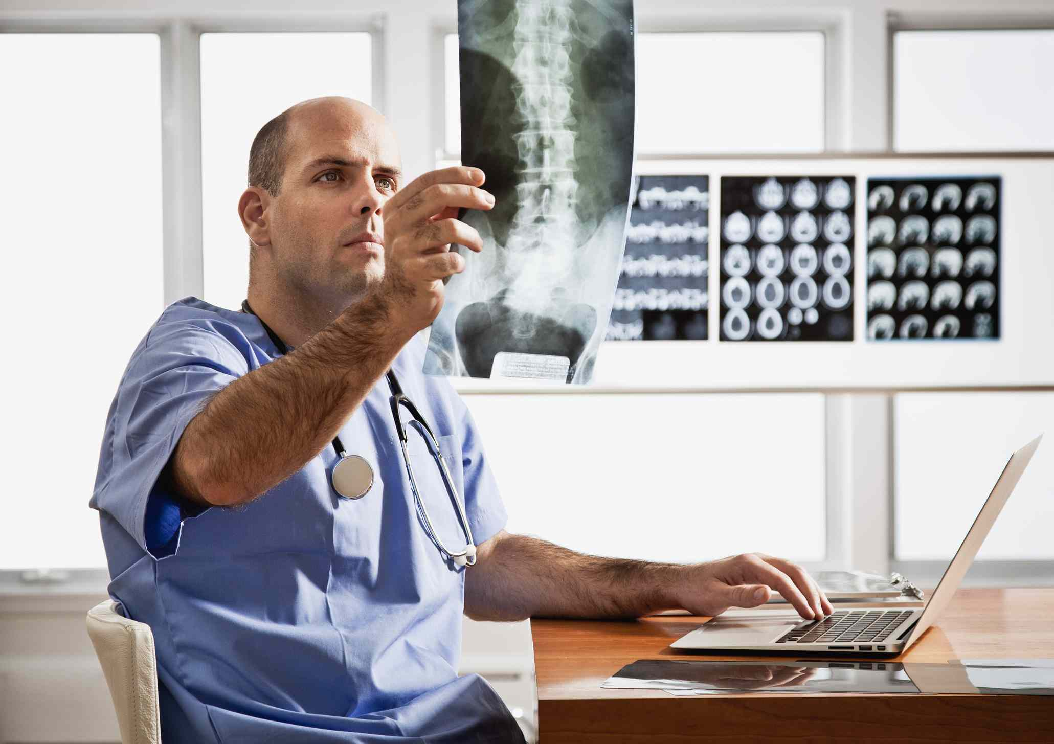 Young doctor in radiology clinic office Young doctor examining spinal chord x-ray in radiology clinic office
