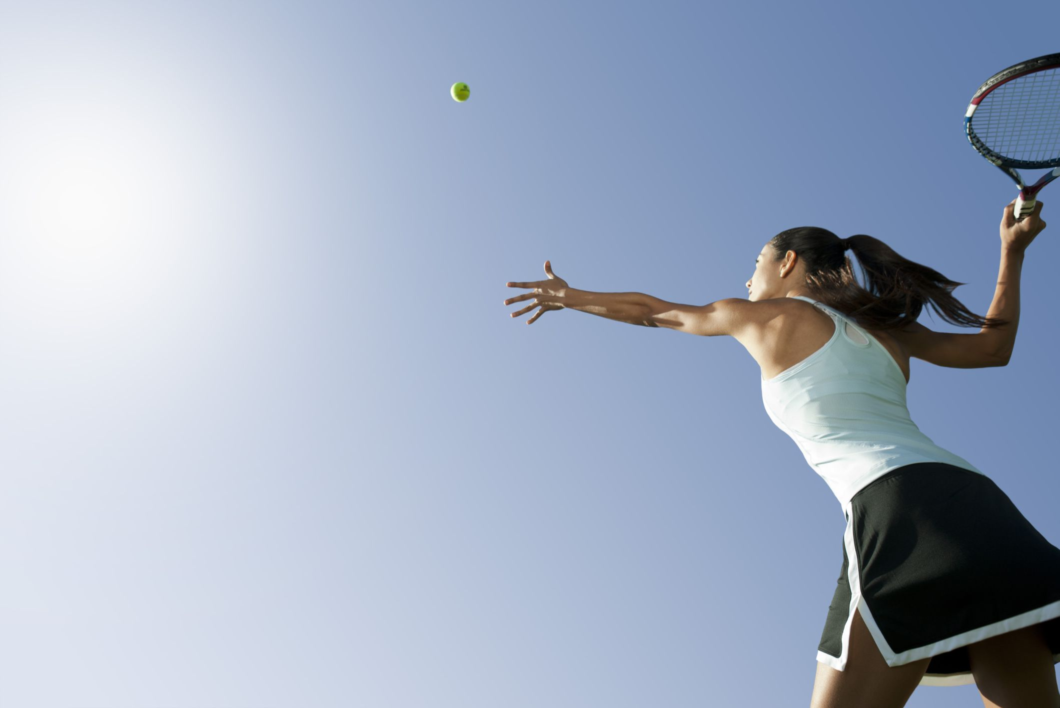 Woman throwing tennis ball in the air getting ready to serve