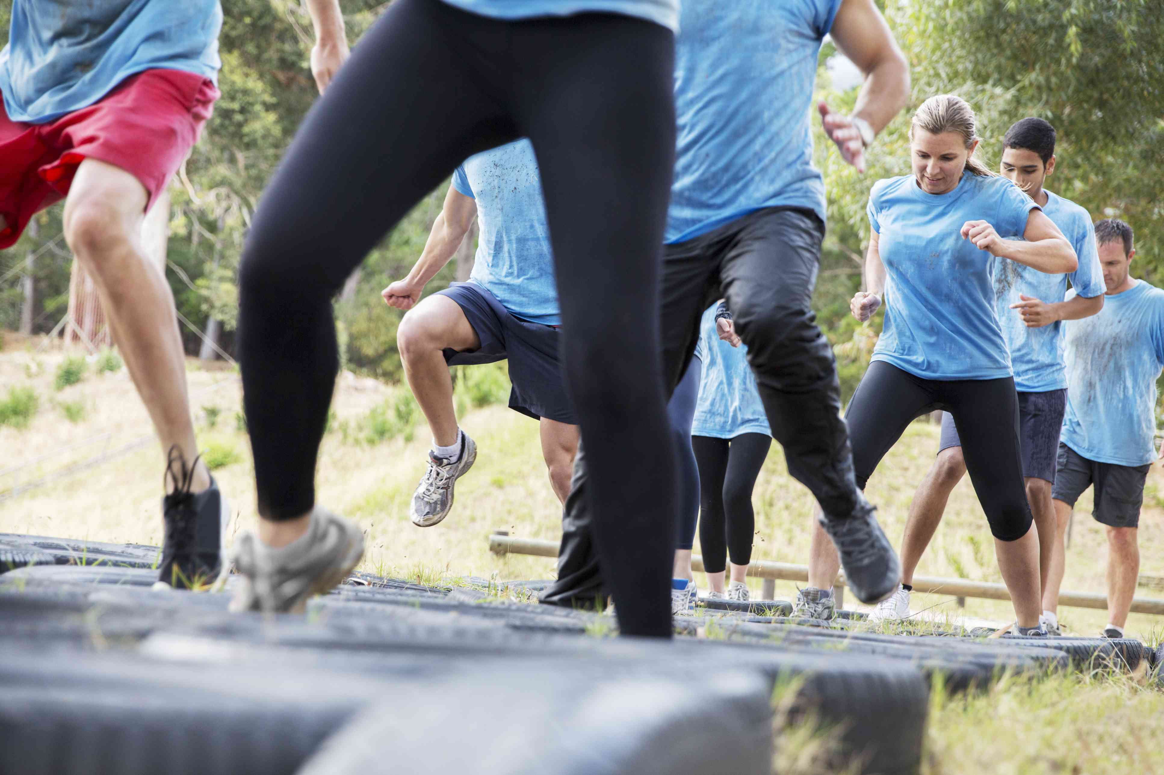 Determined people jumping tires on boot camp obstacle course