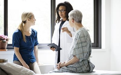 A woman and her daughter talking to their doctor