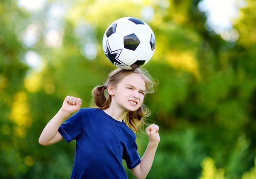 Girl heading soccer ball