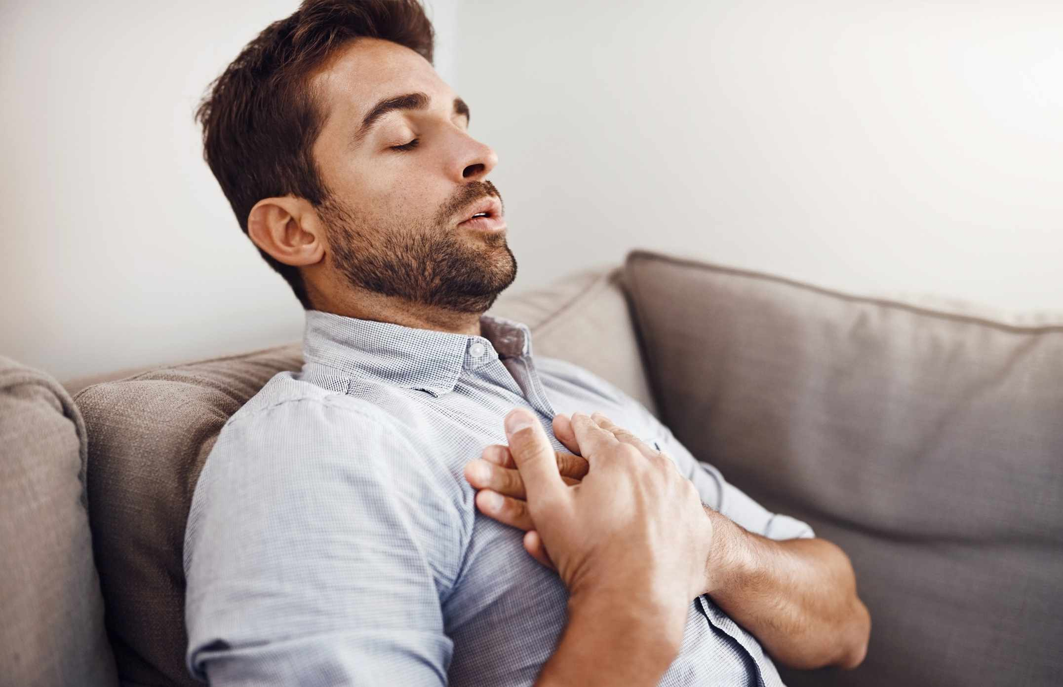 Man holding chest and wheezing