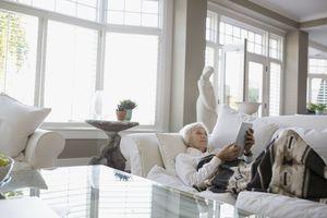 Relaxed senior woman digital tablet living room sofa