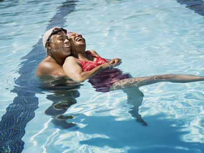 Senior man and woman in a pool holding each other