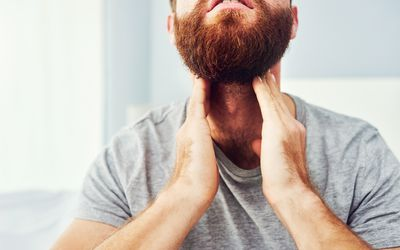 Person with a beard touching their throat as though it hurts