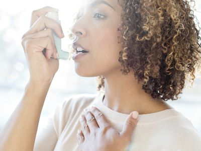 Mid adult woman using inhaler