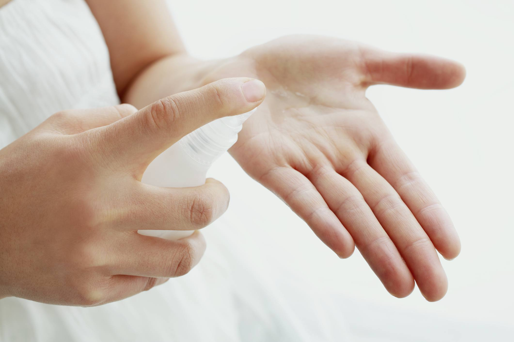 Woman pouring medicated cream into hand, close-up