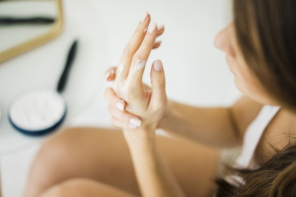 Woman applying hand lotion