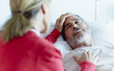 a woman stroking an older man's head in hospital