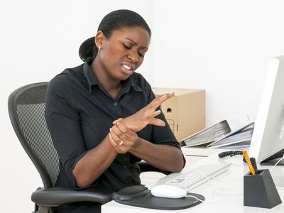 Woman sitting at a desk and rubbing her wrist in pain