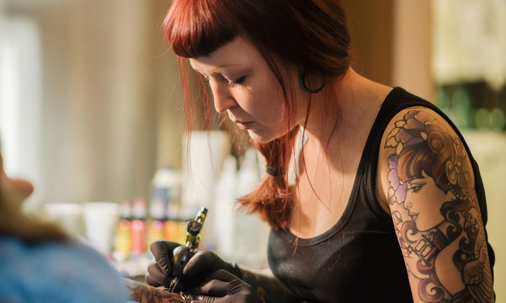 A female tattoo artist working on a customer
