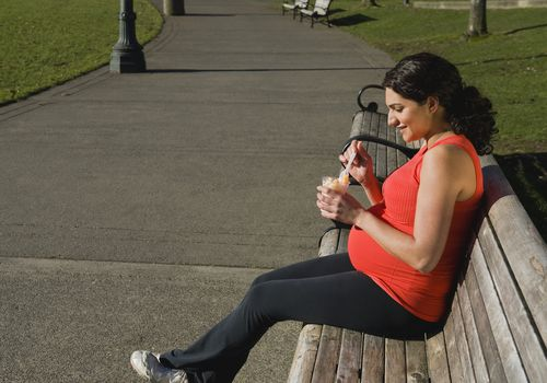 Pregnant woman eating fruit in a park