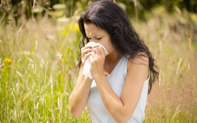 Girl wiping nose with tissue in a field