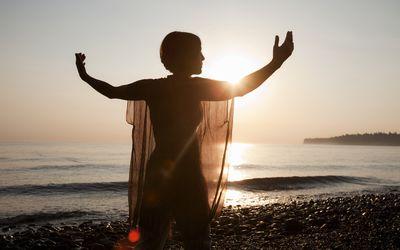 Woman doing qigong on the beach