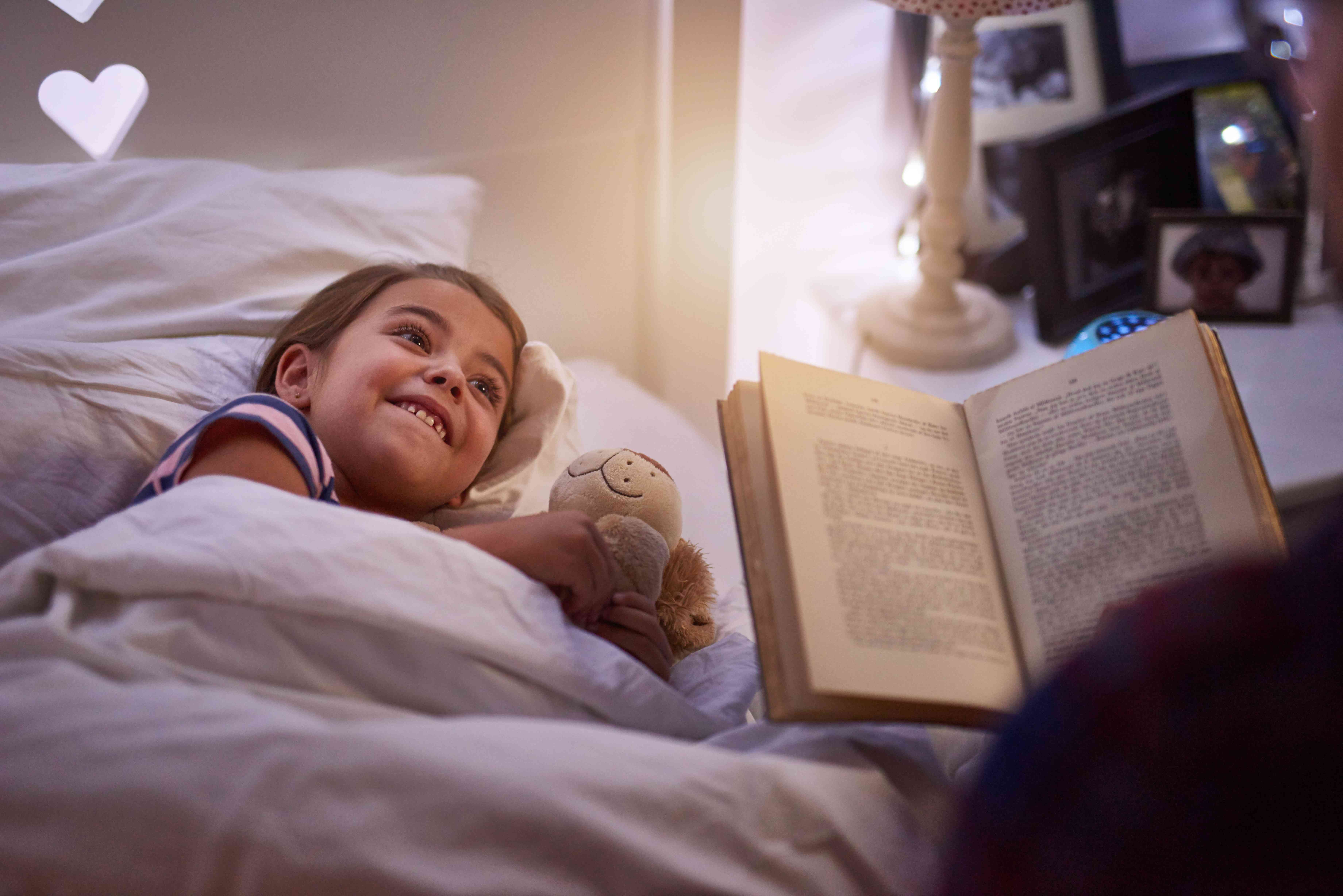 Young girl in bed while parent reads to her