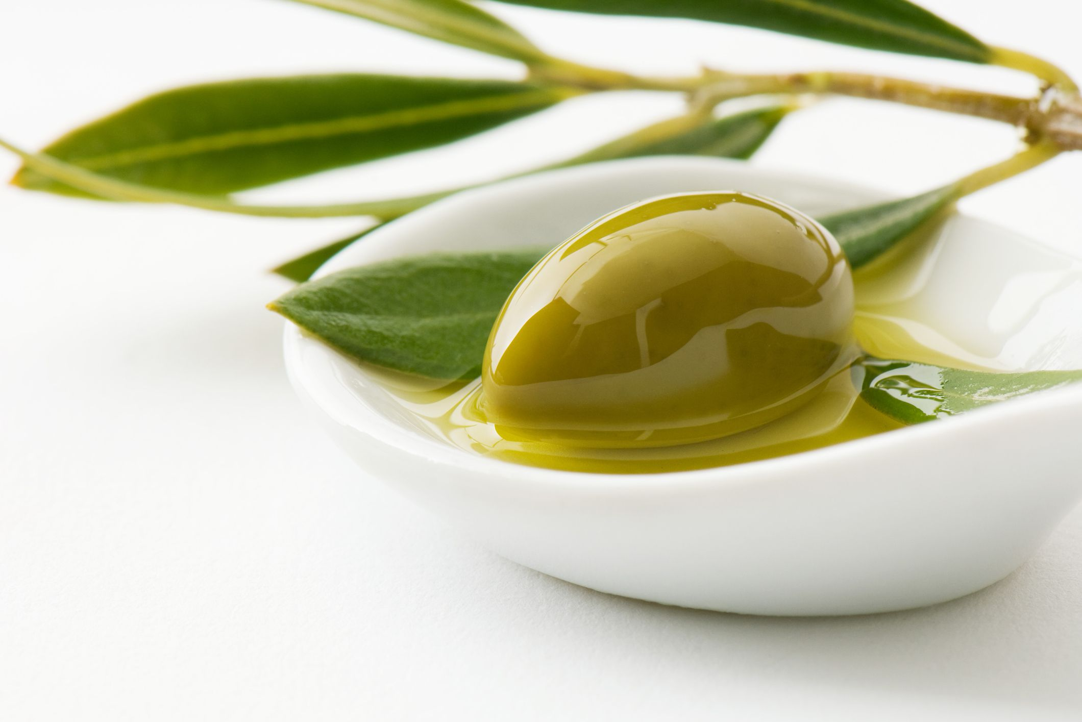 Olive sitting in cup of olive oil