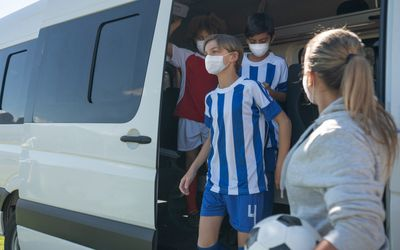 Kids arriving at a soccer camp with face masks.