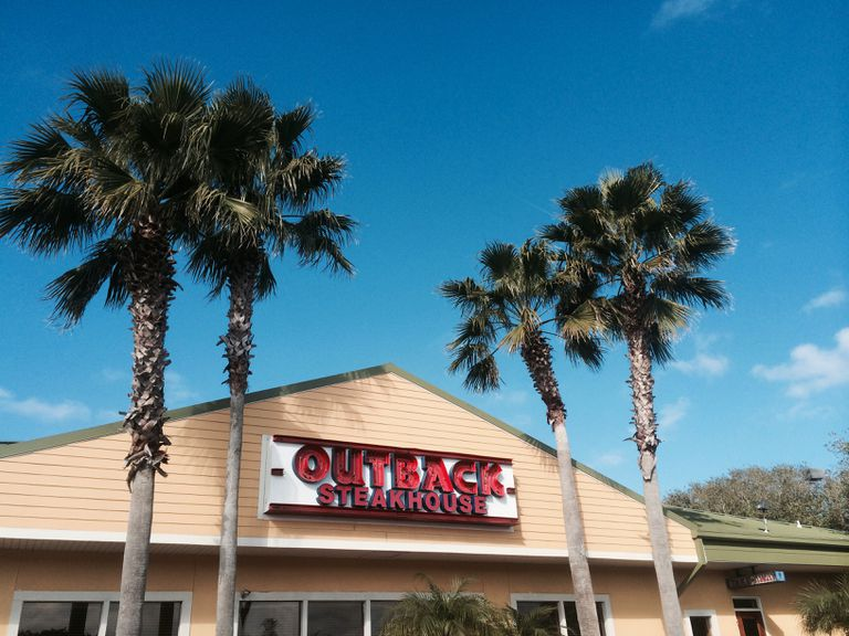 Outback Steakhouse building with palm trees in front