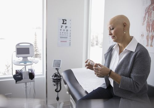 Bald female cancer patient reading label on prescription medication bottle in clinic examination room