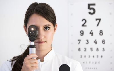 Ophthalmic practitioner holding device to her own eye