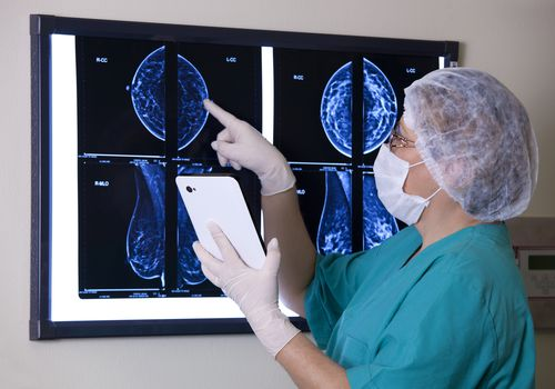 doctor in mask holding ipad looking at mammogram scans