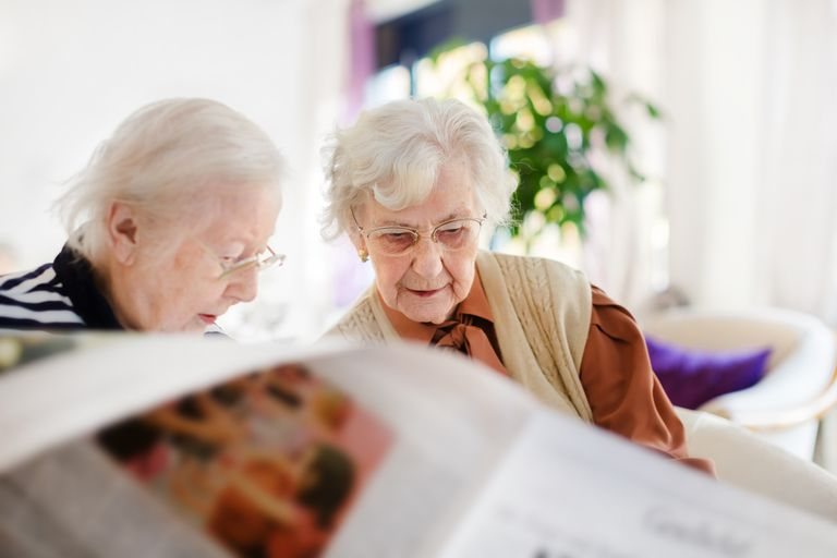 Two Senior Woman Reading Newspaper
