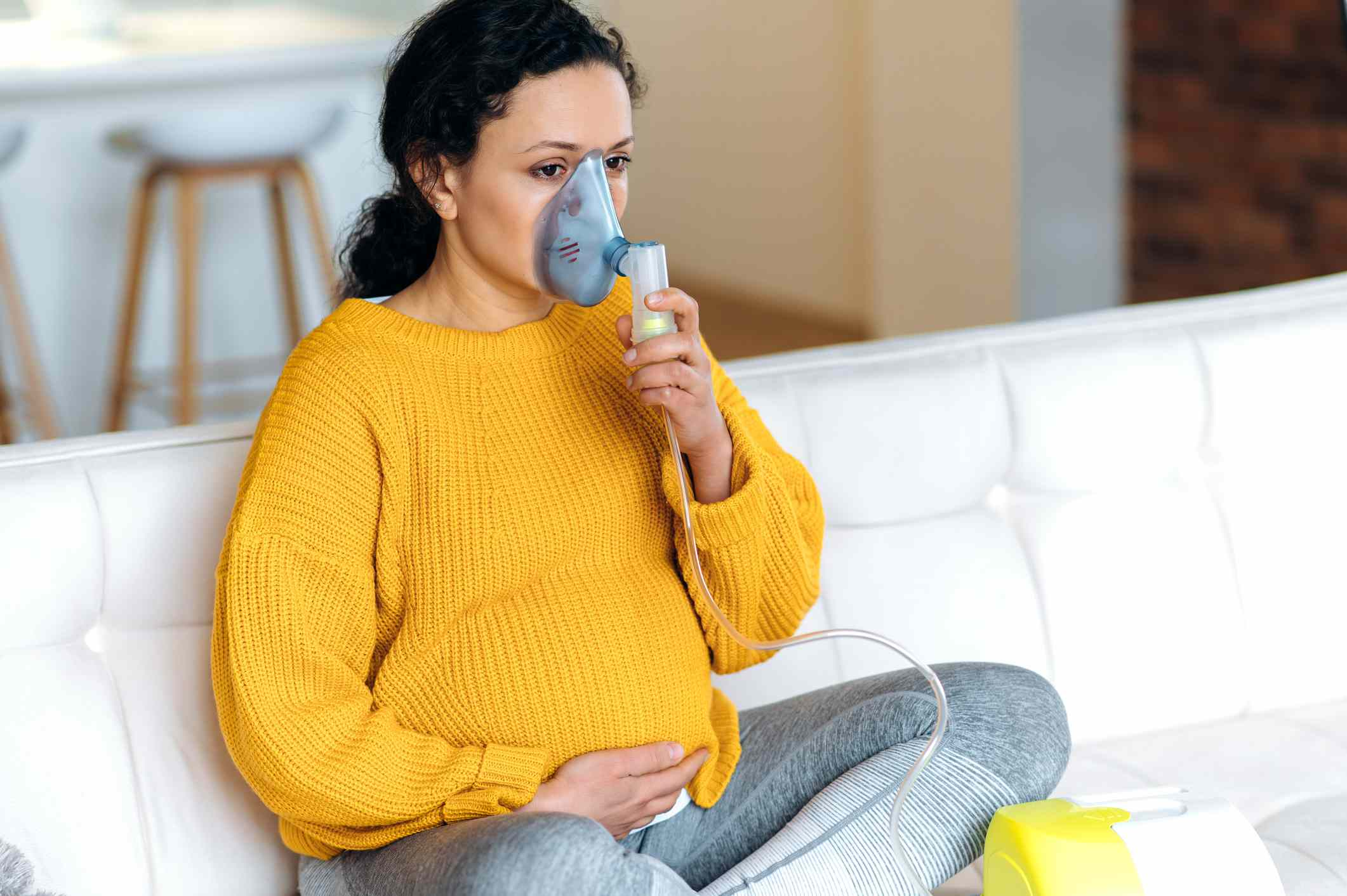woman using an inhaler with a spacer